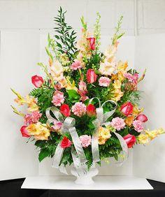 Joe's sympathy arrangement with gladiolus, standard roses, carnations, larkspur, and leather leaf, plumeria, and tree fern embellishments