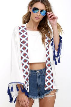 We're hitting the highway in our favorite cutoffs and the vacation-ready Desert Delights Ivory Fringe Kimono Top! Gauzy woven rayon falls to long sleeves trimmed in blue embroidery and tassels. Panels of more blue and red geometric embroidery decorate the open front.