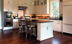 Island-shaped traditional, transitional kitchen featuring white cabinets and white accents.
