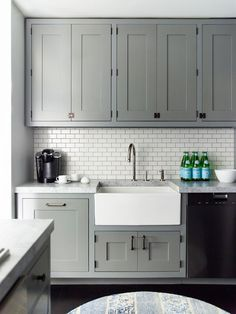 Kitchen: grey cabinets, apron sink, white subway tile back splash, and light countertops