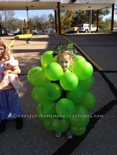 """Her """"bunch -o -grapes"""" costume was created simply (and afford -ably) with green balloons, a bit of artificial/plastic greenery, and Homemade Halloween Costumes, Halloween 2013, Holidays Halloween, Halloween Ideas, Halloween Stuff, Grapes Costume, Fruit Costumes, Diy Costumes, Costume Ideas"""