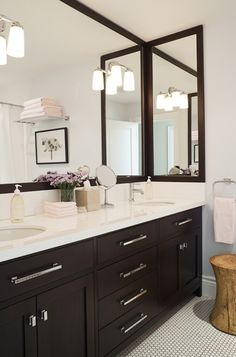 Jennifer Worts Design  Modern espresso bathroom design with espresso double vanity, chrome modern pulls hardware, marble countertops, espresso stained framed mirrors, penny tiles floors and grey walls with navy blue accents