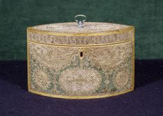 """A George III Gilt and Polychrome Quillwork Tea Caddy,   CIRCA 1790,   Height: 5"""" - Of elliptical form; with stylized floral and foliate decoration; opening to a lidded compartment inlaid with a burr yew oval panel."""