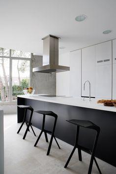 Cuisine minimaliste en blanc et noir - j'aime le contraste des meubles blancs côté cuisine et du noir côté bar (y compris les tabourets design)