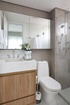 Banheiro com pastilhas exagonais, bancada em pedra branca, cuba de embutir, gabinete de madeira, armário suspenso com portas de espelho, bacia sanitária, chuveiro cromado, papeleira de chão. Banheiro decorado, decoração. Reforma e decoracao apto completo