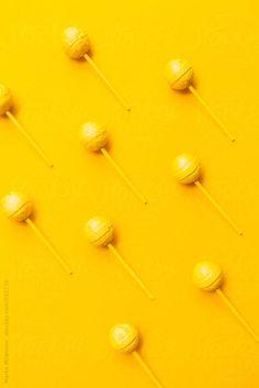 Minimalistic yellow lollipop on yellow background by Marko Milanovic on STOCKSY