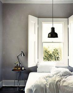 Grå vægge, hvid indretning og sort lampe