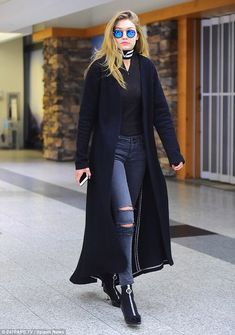 Jet-setting chic: The latest Victoria's Secret recruit looked nothing short of sensational in a pair of ripped skinny jeans, a plain black top and a flowing duster coat