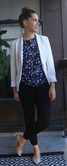 Cute outfit for work: floral top, white blazer, black pants, gray flats.