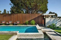 jardín con piscina y valla alta de madera