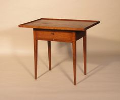 USA | Shaker One Drawer Work Stand.  Two board tray top, mortised case with a dovetailed drawer, square tapered legs.  The six turned bone hangers were meant to support a hanging work bag or a number of sewing tools.  Butternut and pine. New Lebanon, NY c. 1840.
