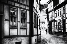 Alone - A man walks alone through the beautiful old town of Stolberg (Harz). The old half-timbered houses are a fantastic backdrop. Impressionist street photography in black and white. #photography #street #streetphotography #impressionist #Harz #Stolberg #blackandwhite