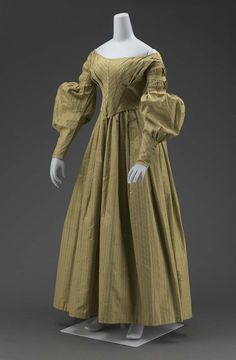 Dress (a) and matching cape (b) of grayish-olive-green silk with fancy-woven stripes with lines of white; fitted bodice, pointed in front; widely flaring neck; fullness across bust in unpressed pleats; long sleeves with fine pleats in upper part held in place by bias folds, full from just above elbow to above wrist, fullness pleated vertically to wrist; full skirt with loose pleats in front and gathered in back; short double cape (b) of same material with edges finished with bias folds of…