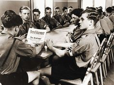 """ORIGINAL CAPTION: """"Hitler Youth were organized into local groups that held weekly meetings that included political indoctrination. Here, a troop leader reads to his fellow Hitler Youth during a social evening. 1937."""""""