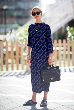 Patterned dress with flat slides and a Chanel bag.