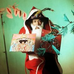 Pictured here is Rock-legend Jimi Hendrix all decked out as Father Christmas while holding up his LP: Axis Bold As Love. This picture was taken during the Christmas season of when Hendrix was promoting the release of his new album. Rock N Roll, Rock & Pop, Pink Floyd, Buster Keaton, Les Beatles, Jimi Hendrix Experience, Easy Guitar, Illustrations, Shows