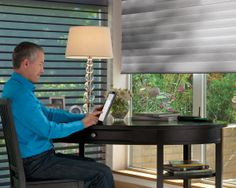 Hunter Douglas Silhouette. In this picture the man is operating his Powered Silhouettes with his Platinum App. on his iPad