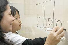 A profesora Silvana D'Ambrosio, do colégio Sion, na cidade de São Paulo, ajuda o aluno Mateus Yoona fazer letra cursiva
