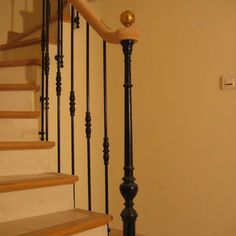 Rampe sur escalier maçonné. Main courante débillardé avec volute de départ Pilastre de départ en fonte et barreaudage en fers forgé.