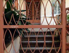 A brown iron gate in Beyoğlu, and behind it a brown iron door