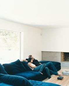 Griffith and LeBlanc cozy up on the Flexform sectional in the den, where one of the home's two original wood-burning fireplaces has received a new concrete hearth and mantel. The room, which is located a half flight of stairs down from the main living are
