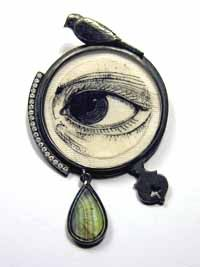 photo of a brooch with an image of an eye in the middle, surrounded by a bird and a green stone by Zoe Arnold