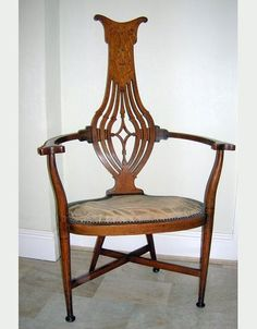 Arts & Crafts Elbow Chair  An absolutely stunning Arts and Crafts chair in inlaid oak.  The chair is raised on round tapering legs terminating in pads, with an offset cross stretcher.