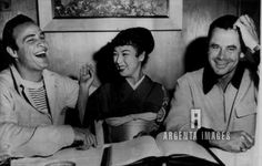 Marlon Brando and Machiko Kyo Japanese actress enjoy a joke during her visit to a movie studio as actor Glenn Ford scratches his head and wonders if he missed the point