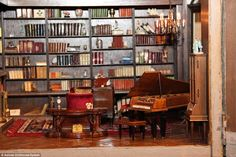 A tiny grand piano is seen in one of the 29 rooms in the dollhouse in this photo along with dozens of mini books