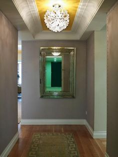 This long and narrow hallway has a yellow painted ceiling. Check out the dot pattern outlining the gray walls!