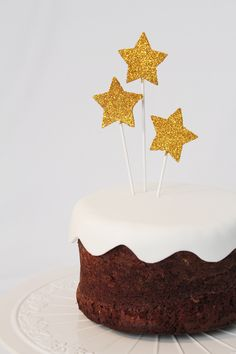 Gold Stars cake toppers could be easy to make out of cardboard, glitter and skewers.