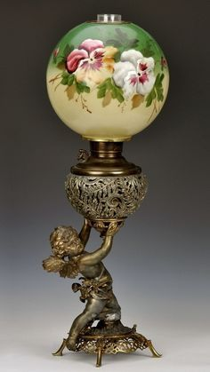 Victorian cast metal parlor oil lamp with cherub base, made by Juno Lamp Co.  What a beautiful lamp.  I am sure the lady of the house would have been very proud to own it.  D. Martin