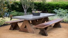 Upscale picnic    Decomposed granite provides a stable surface for this sophisticated picnic table from Artefact Design & Salvage. Offering some shade are three fruiting olives--one of several ornamental edibles that designer Stefani Bittner snuck into the design.