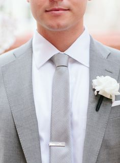 My groom in a Brooks Brothers light grey suit, skinny silver tie/tie bar from the Tie Bar and a white ranunculus boutonniere.