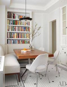 Michael J. Fox and Tracy Pollan's Manhattan Home : Architectural Digest. In the breakfast room, the Lightolier pendant lamp and the table, a teak partners desk by Florence Knoll, are both from Wyeth; the banquette is covered in a Lee Jofa linen, Saarinen Chair, Banquette Design, Corner Banquette, Sweet Home, Kitchen Nook, Kitchen Booths, Banquette Seating In Kitchen, Built In Dining Room Seating, Kitchen Bookcase