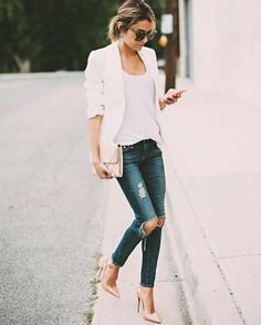 Christine Andrew combines ripped denim jeans with a white cami and blazer to create a smart/casual street style perfect for spring. She has chosen to wear this style with nude stilettos. Brands not specified.