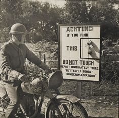 A passing despatch rider, on a Matchless Model GL3, reads a beachhead sign warning against butterfly bombs, Normandy, 1944. The German butterfly bomb was a highly effective two-kilogram anti-personnel weapon dropped by aircraft. Containers holding between six and 108 bombs were released from an aircraft and would then burst open, scattering their contents over a wide area. The device was a precursor of modern cluster bombs.