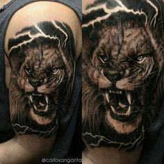 Realistic lion tattoo on the left upper arm.