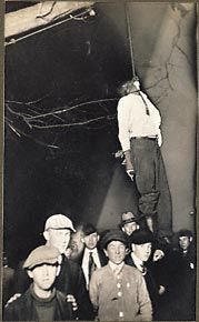 Lynching of gagged black male hanging from a tree in autumn. Large crowd of onlookers, mostly young boys. Circa 1920, location unknown. ONLY GOD KNOWS.