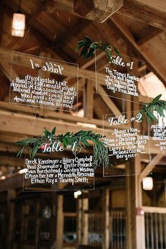 Hang plexiglass signs surrounded by greenery from your venue's ceiling to create super cool floating seating charts.