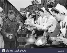 """Stock Photo - German Red Cross (DRK) nurses take care of the troops - the Nazi Propaganda! on the back of the image is dated February """" A DRK helper gives out warm food to soldiers who History Of Germany, Zombie Nurse, History Of Nursing, Nazi Propaganda, German Girls, Vintage Nurse, Luftwaffe, Red Cross, Women In History"""