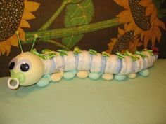 "Diaper catepillar:  This critter calls for diapers, socks, beanies, pacifiers & other secret crafting items. When finished, ""Cuddles"" measures over 2 feet long!    Moms can never have enough baby socks. So what better way to give a practical gift of 9 pairs of brand new infant socks in the form of a cute-n-cuddley caterpillar?"