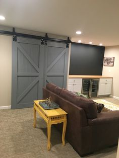 DIY barn doors built by my husband. Perfect for hiding laundry area in our finished basement. Bar with wood top, clear refrigerators and chalkboard paint wall.