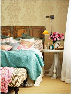 I see a few things in this bedroom that I like a lot.  The old door used as a headboard, the wallpaper, the unusual light, the colors and fabric.  Comfy room!