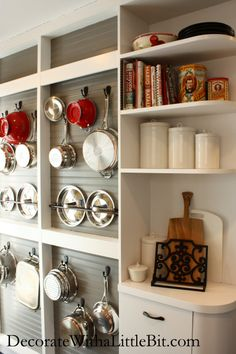 great wall of pots! love using cookware as a design/art piece in the kitchen. they took the fronts off of the shallow cabinets and made them open storage for pans