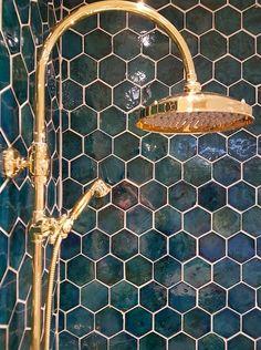 Shower wall tiles and brass shower head. Bathroom interior design and decor. Shower wall tiles and brass shower head. Bathroom interior design and decor.