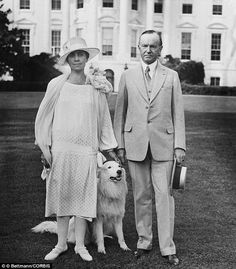 Calvin Coolidge and his wife pose with one their six dogs on the White House lawn