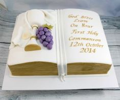 Holy communion cake in the shape of a bible, with hand made fully edible chalice,grapes, host and cloth. Edges , lettering and trim on chalice were hand painted with edible gold paint. First Holy Communion Cake, First Communion Cakes, Recuerdos Primera Comunion Ideas, Open Book Cakes, Comunion Cakes, Cake Paris, Bible Cake, Fondant Flower Tutorial, First Communion Decorations