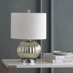 Mercury glass was prized as one of the first decorative styles of glass in an era where the material was used to be utilitarian. This lamp base presents a modern interpretation of the mercury glass effect with a silver sprayed interior and beautiful variegated ribbing on the round body. #tablelamp #tablelighting