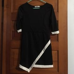 Black and white new asymmetrical dress This dress  is brand new and is gorgeous with it asymmetrical hem and white highlights on the cuffs.It says size large but runs small so I would say size  is a more like a medium. Stan Heritage Dresses Asymmetrical